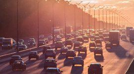 Coches circulando con mucho tráfico en la entrada a una ciudad con contaminación.